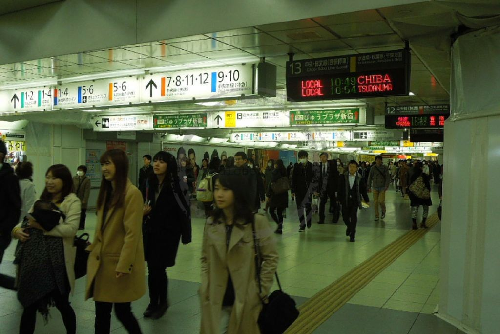 Busy station in Tokyo with indication of several train lines and exits